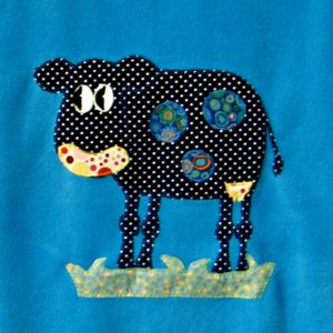 Blue baby fleece blanket with black and white polka dot cow motif